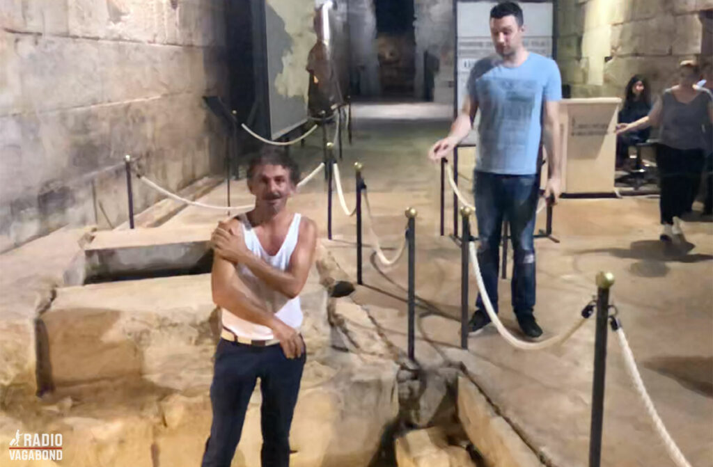 One of the locals washes his face in the wishing well and goes berserk when the guard (on the right) tells him to leave.