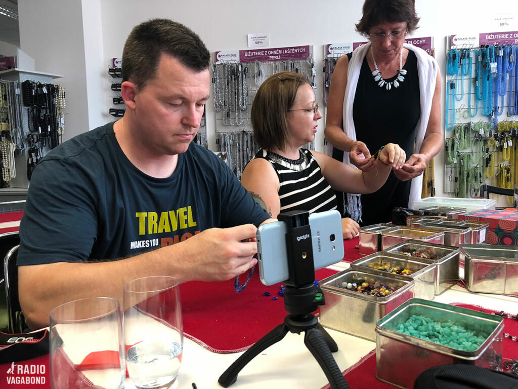 Focussed travel bloggers threading beads.